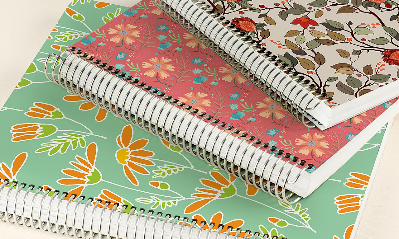 Three Agendio spiral-bound planners with customizable covers
